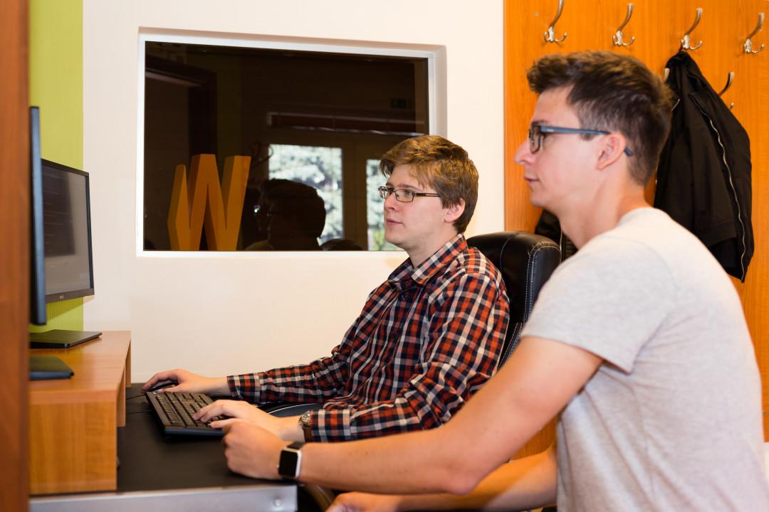 webfejlesztő és projektmenedzser dolgoznak az egyedi weboldal készítési projekten